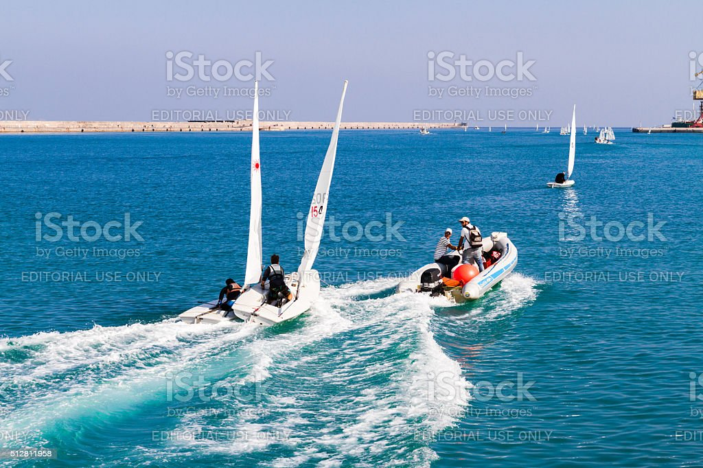 Unexpected sailing accident of two towed speeding beginners laser boats stock photo