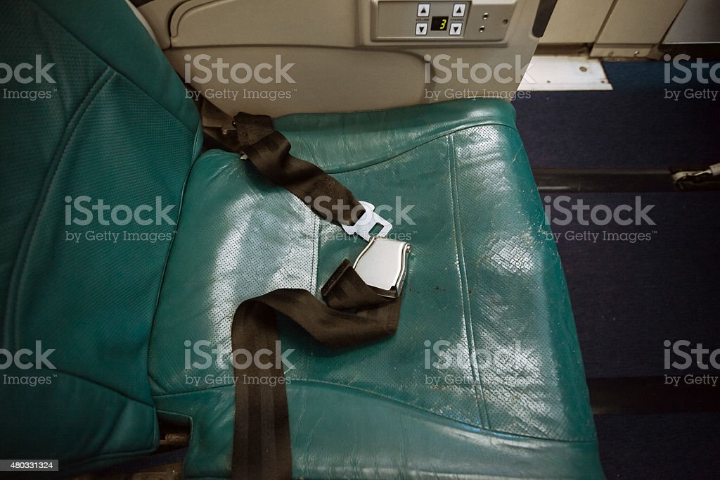 unfastened belt on seat at airplane stock photo