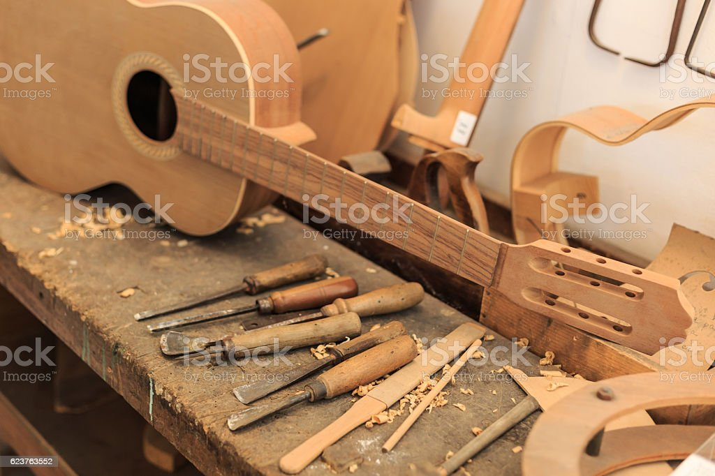 Unfinished acustic guitar and tools in workshop stock photo