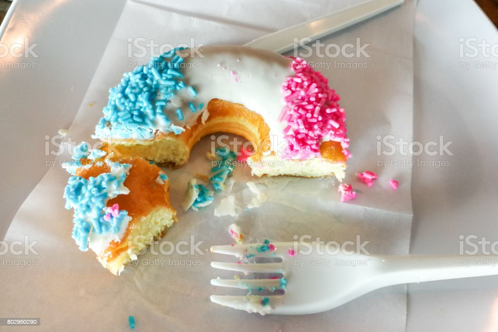 Unfinished donut glazed with sugar coating and sprinkles on plate stock photo