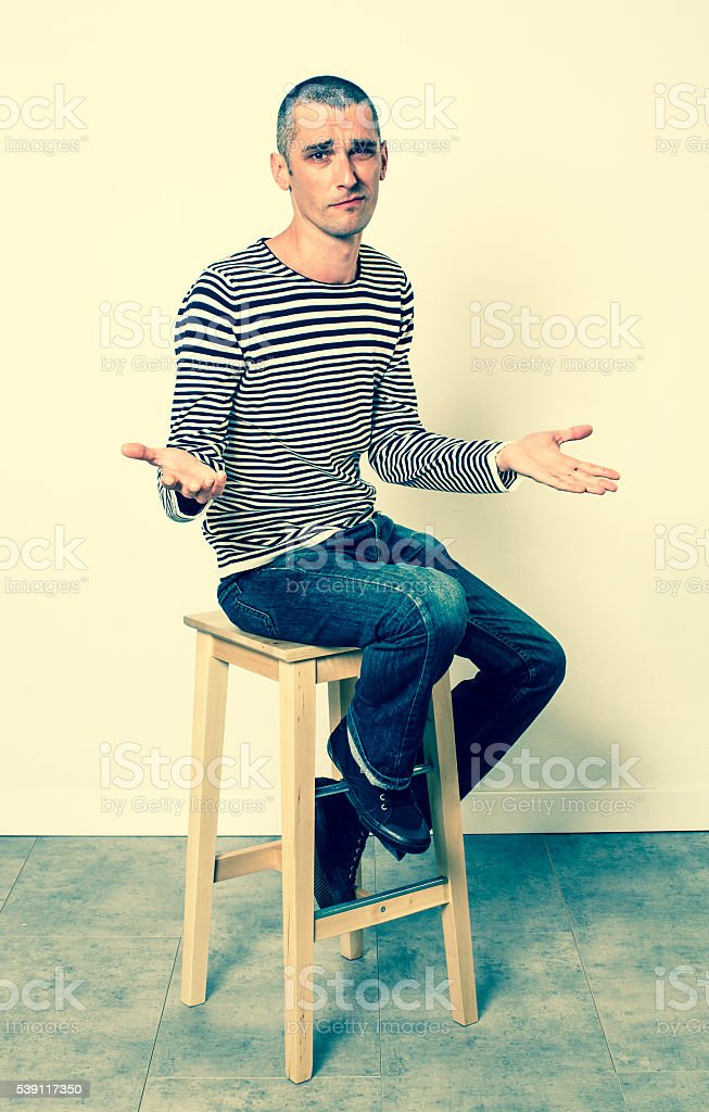 unhappy 30s man with short hair discussing and complaining, sitting stock photo