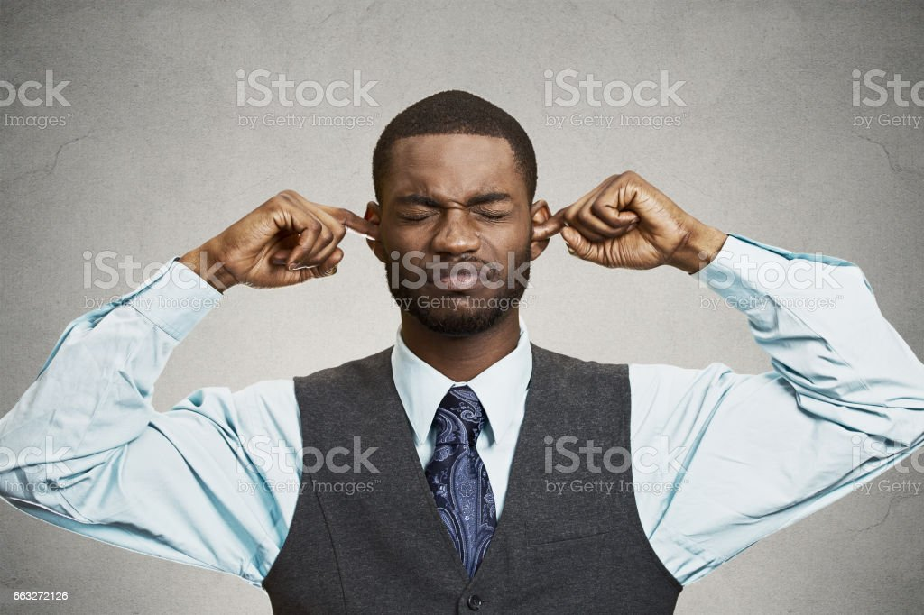 unhappy, annoyed man plugging closing ears with fingers, stock photo