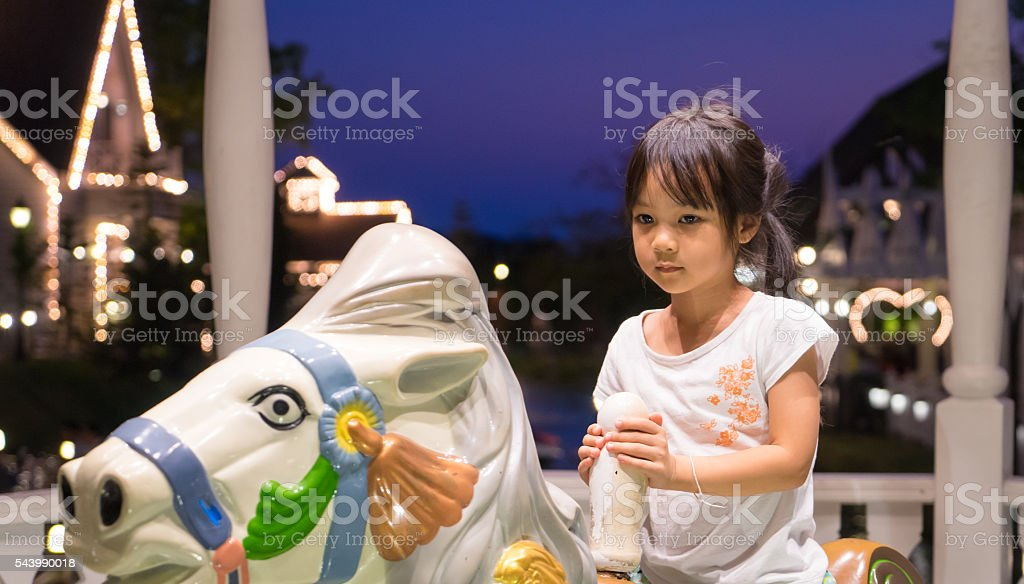 Unhappy Asian girl riding on a house merry go round. stock photo