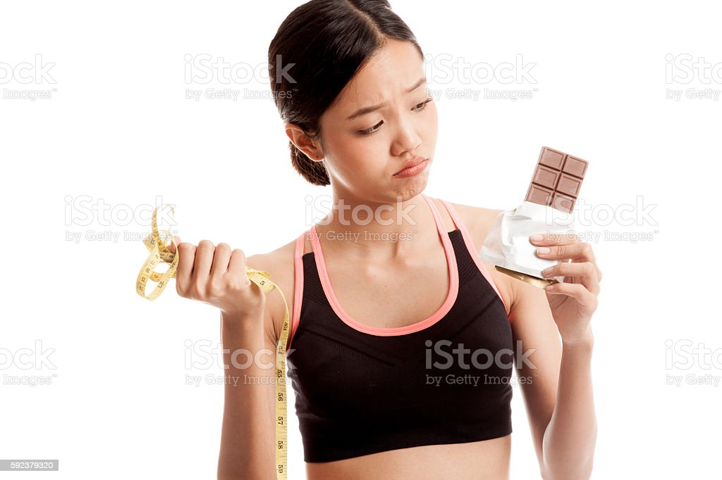 Unhappy Asian healthy girl with chocolate and measuring tape stock photo