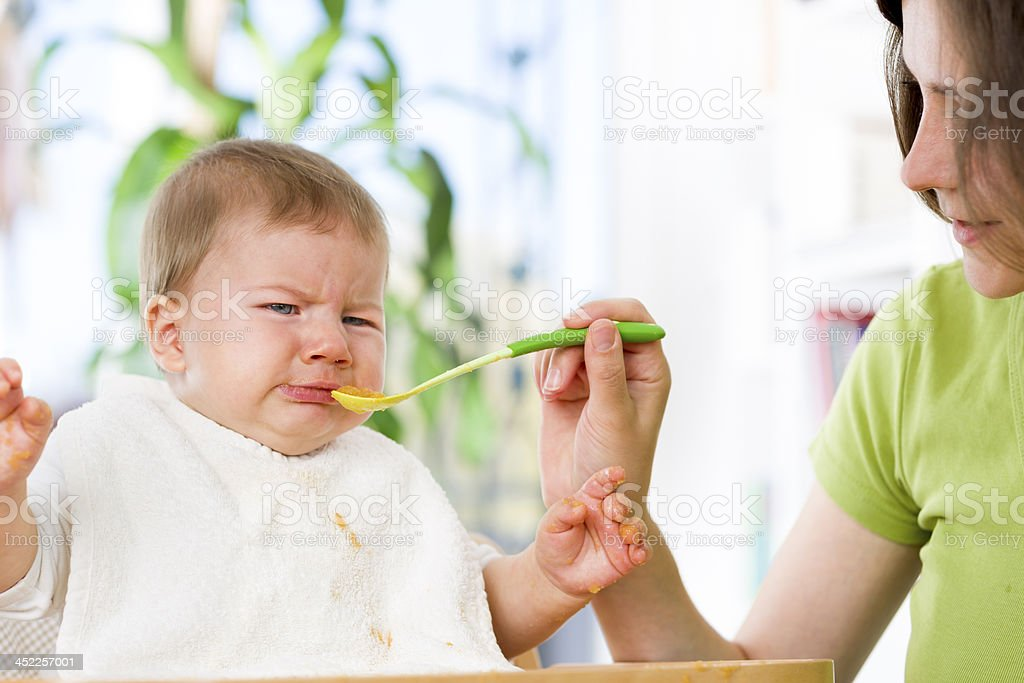 Unhappy baby boy refusing to eat food. stock photo