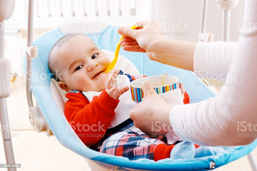 Unhappy baby boy refusing to eat food stock photo