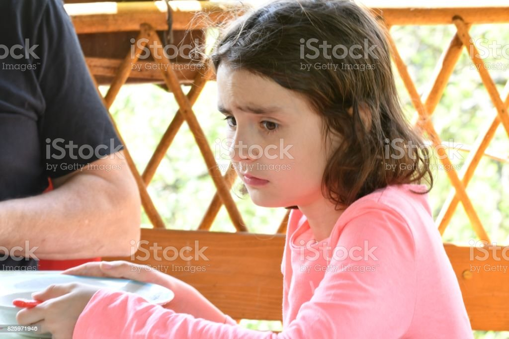 Unhappy baby girl by lunch stock photo