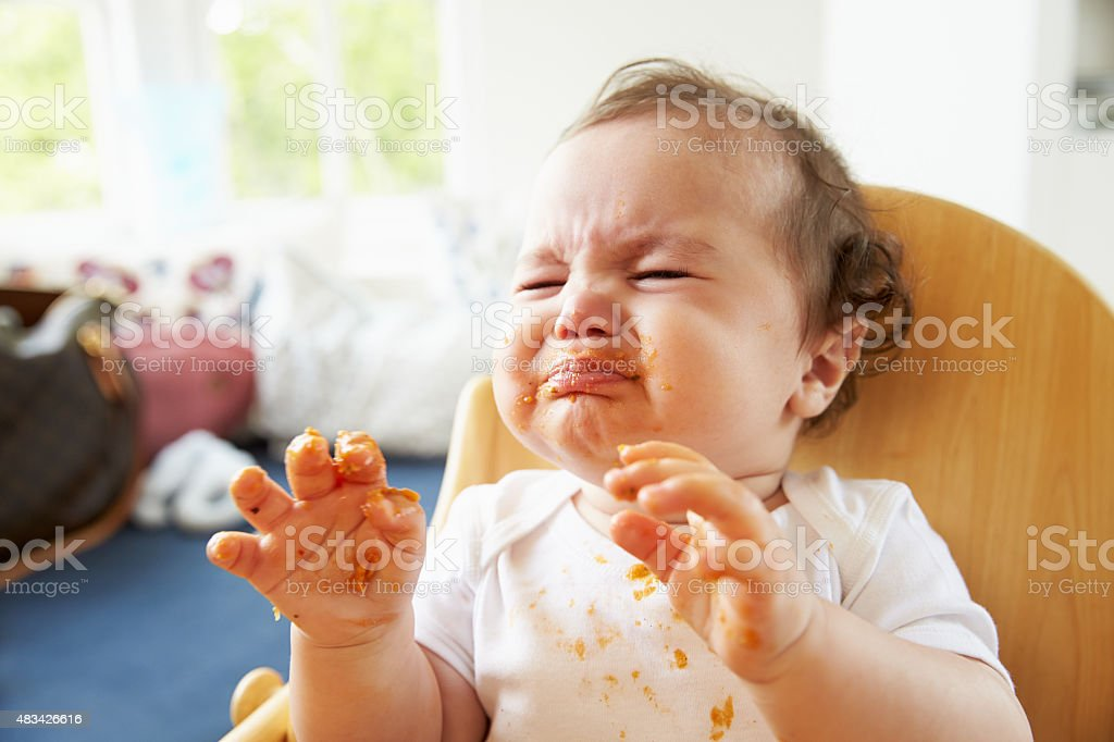 Unhappy Baby In High Chair At Meal Time stock photo