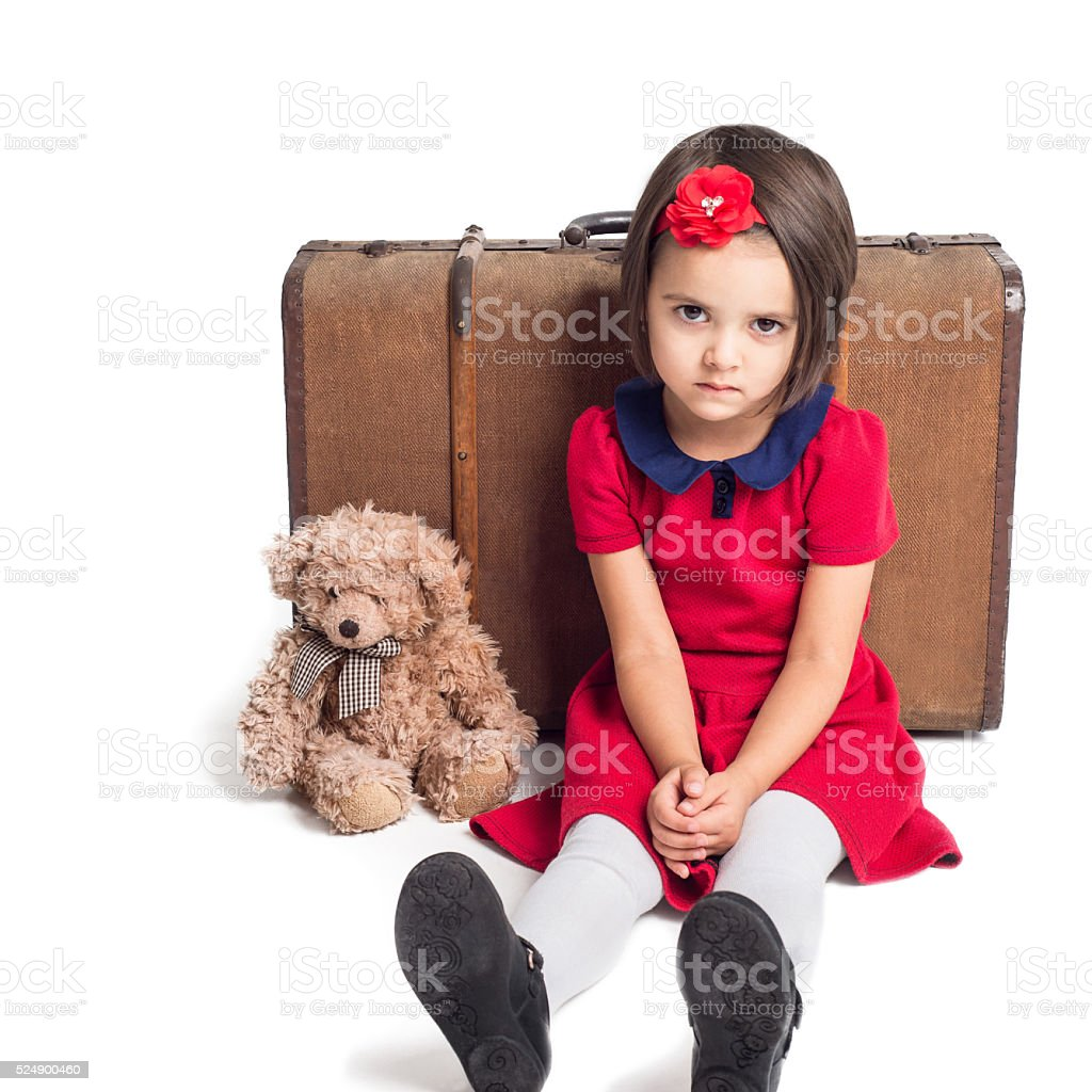 Unhappy beautiful little Girl with suitcase and toy bear stock photo