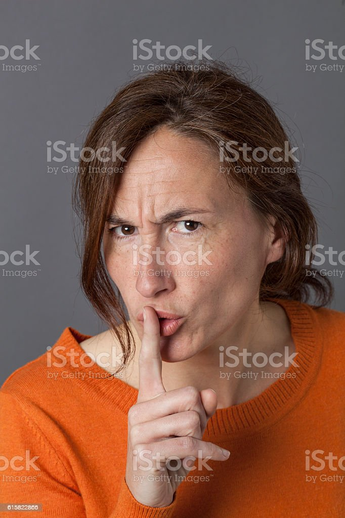 unhappy beautiful middle aged woman requiring silence, discretion or warning stock photo