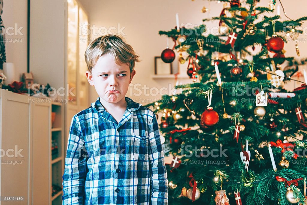 Unhappy boy stands before chistmas tree and makes a face stock photo