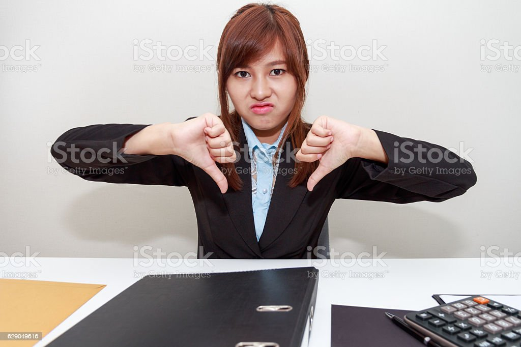 Unhappy business woman with thumb down in office stock photo