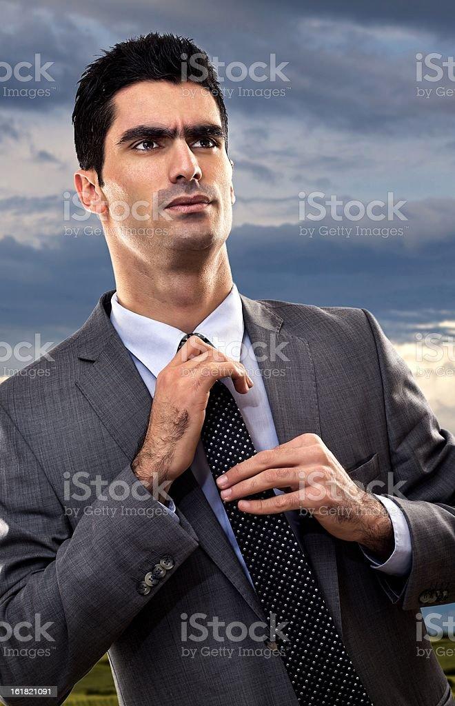 Unhappy businessman correcting tie royalty-free stock photo