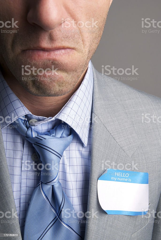 Unhappy Businessman Frowns with Name Tag royalty-free stock photo