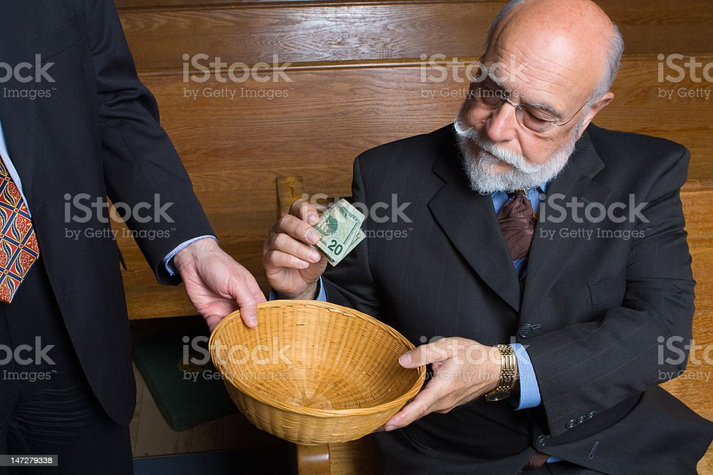 Unhappy Caucasian Senior Man Making Donation to Church Offering Basket stock photo