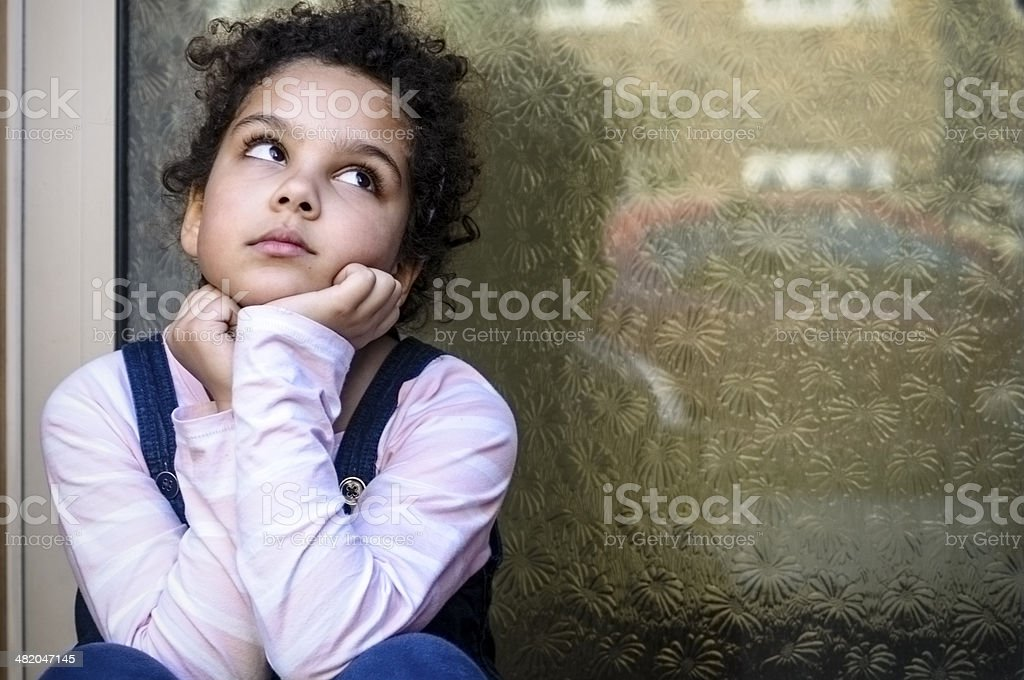 PEOPLE: Unhappy Child (7-8) With Hand On Chin Sitting Outside stock photo