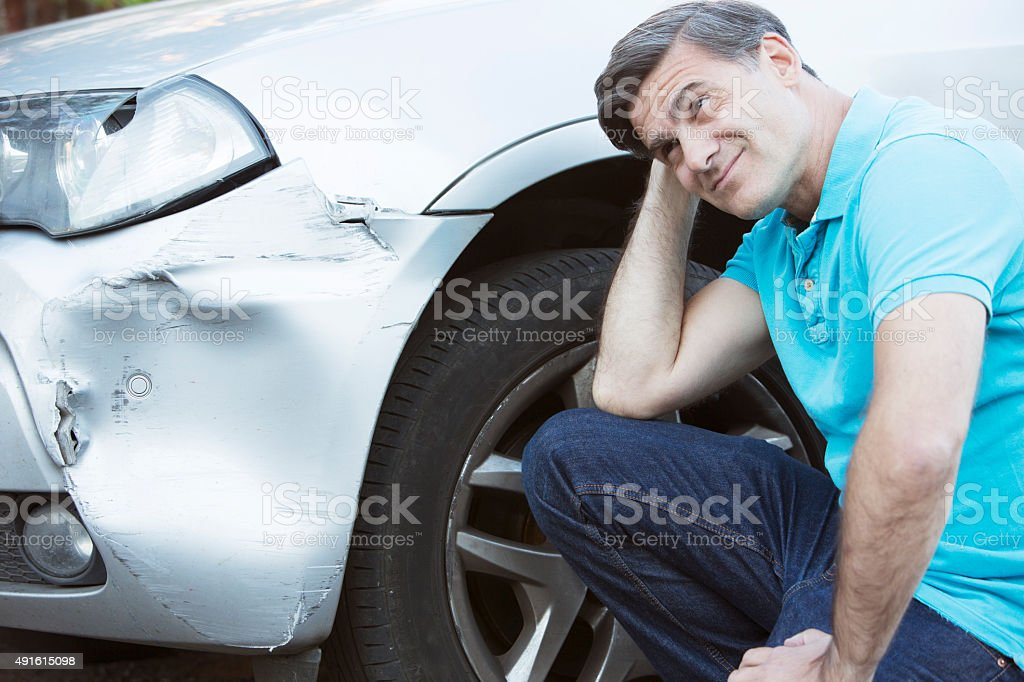 Unhappy Driver Inspecting Damage After Car Accident stock photo