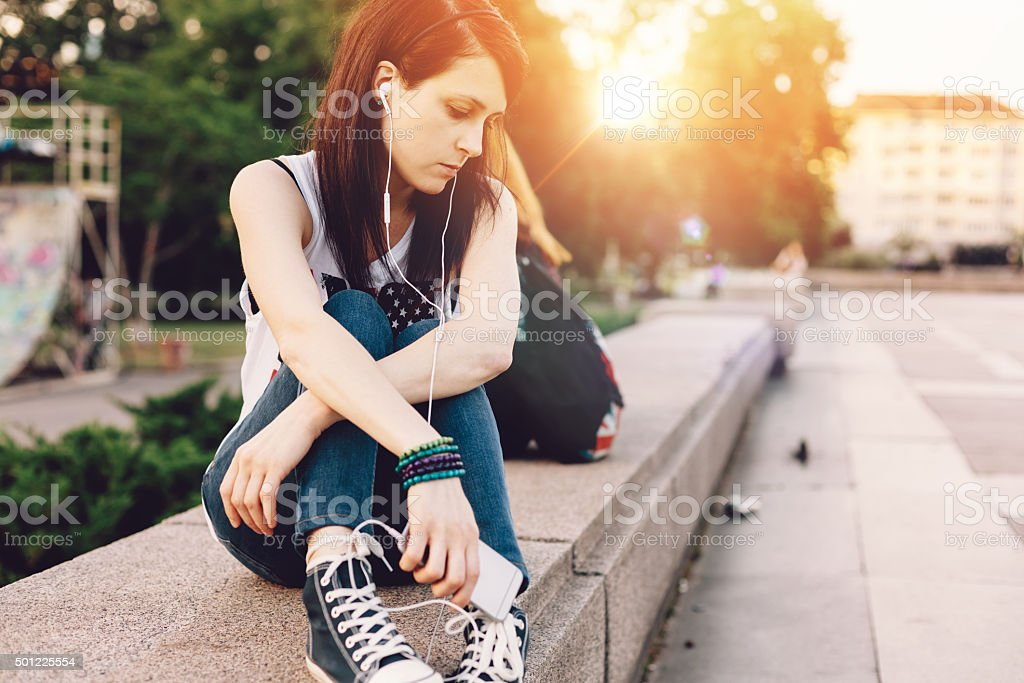 Unhappy girl listening to the music in the city stock photo