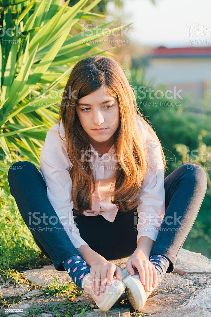 Unhappy girl sitting outdoors in the garden stock photo