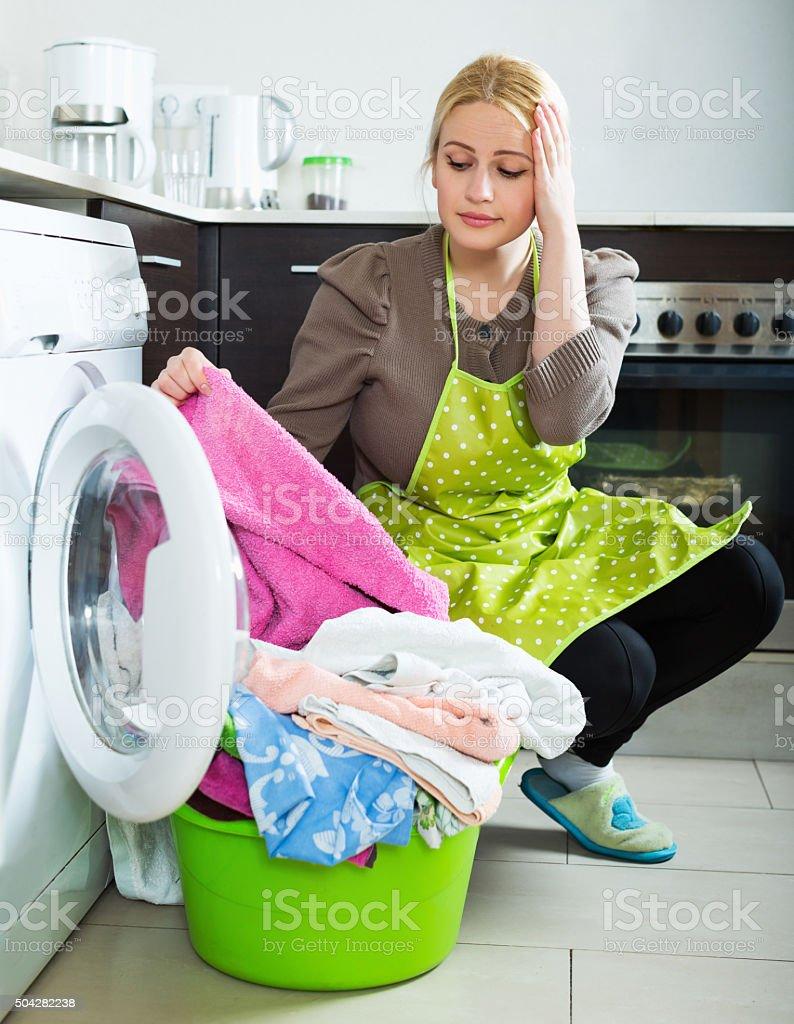 Unhappy girl using washing machine stock photo