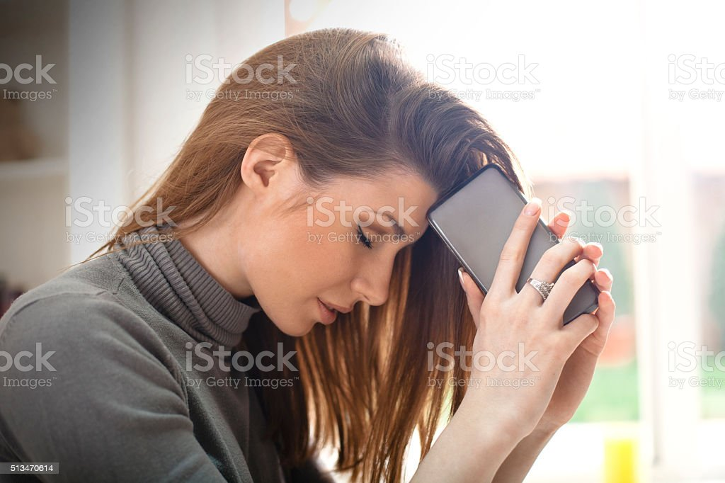 Unhappy girl with mobile phone stock photo