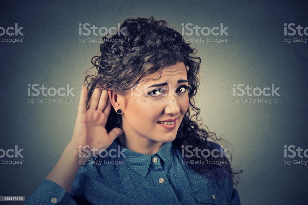 unhappy hard of hearing woman placing hand on ear stock photo