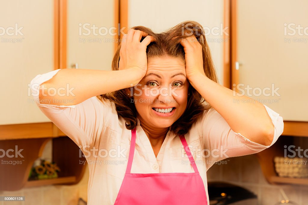Unhappy housewife in kitchen stock photo