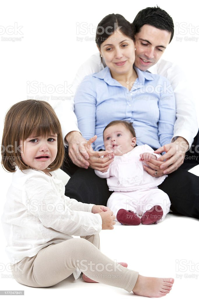 Unhappy jealous little girl with family stock photo