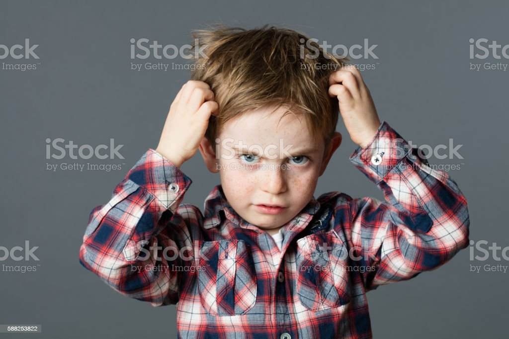 unhappy kid scratching his hair for head lice or allergies stock photo
