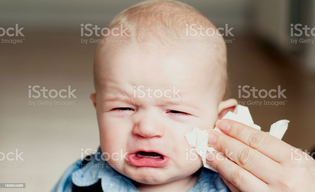 Unhappy little boy gets his nose wiped stock photo