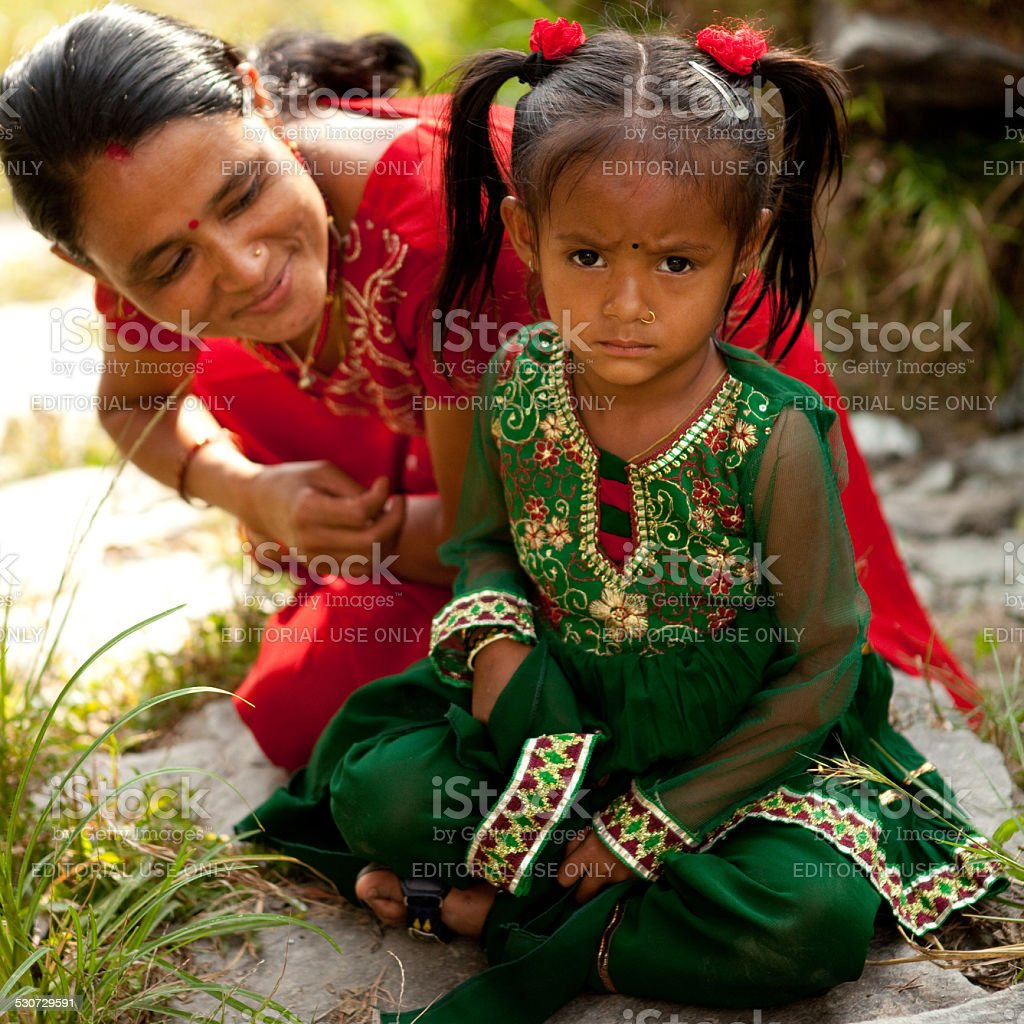 Unhappy little girl in traditional Nepalese dress. stock photo
