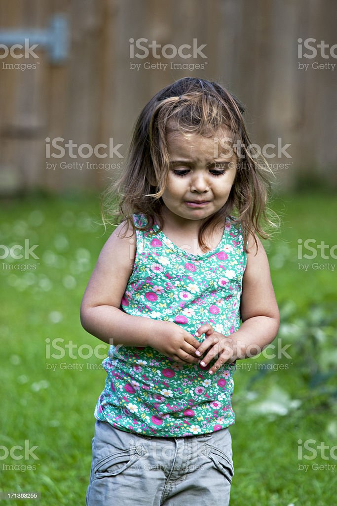 Unhappy little girl standing outside royalty-free stock photo