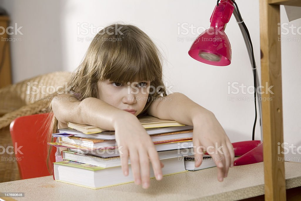 Unhappy little girl studying at the desk royalty-free stock photo