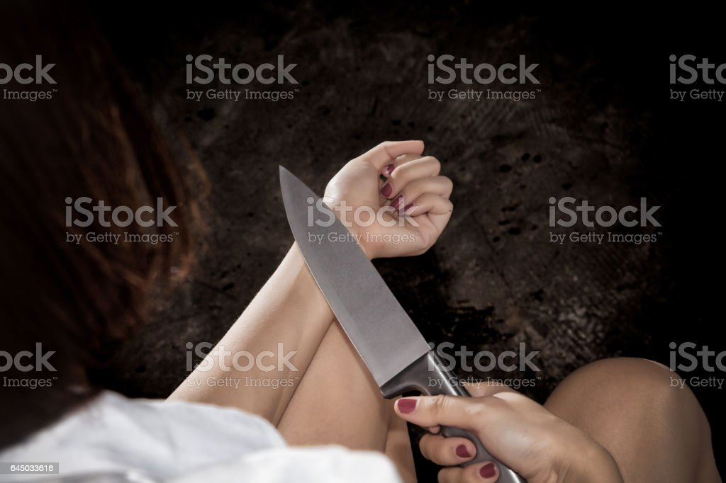 Unhappy lonely depressed woman sitting on old couch, holding knife...