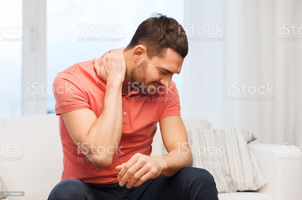unhappy man suffering from neck pain at home stock photo