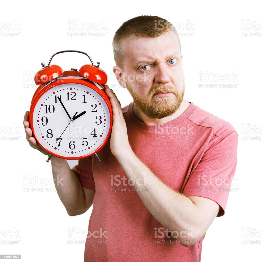 Unhappy man with a red alarm clock in his hand stock photo