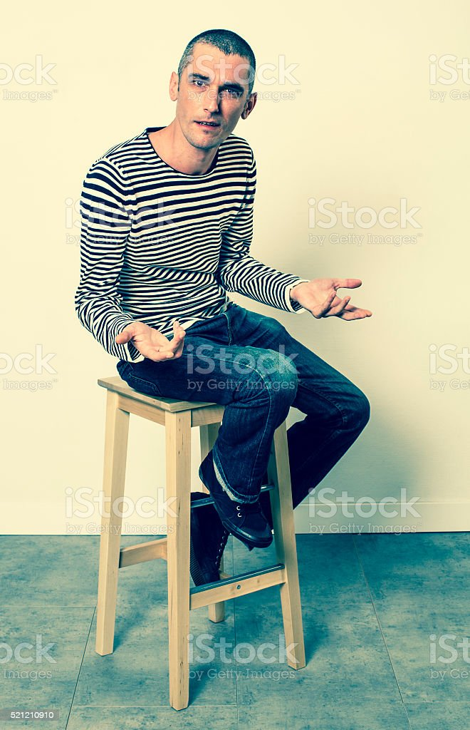 unhappy man with short hair talking with his hands sitting stock photo