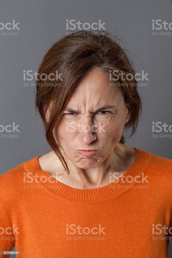 unhappy middle aged woman grumbling and pouting, expressing anger stock photo