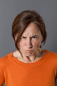 unhappy middle aged woman grumbling and pouting, expressing anger