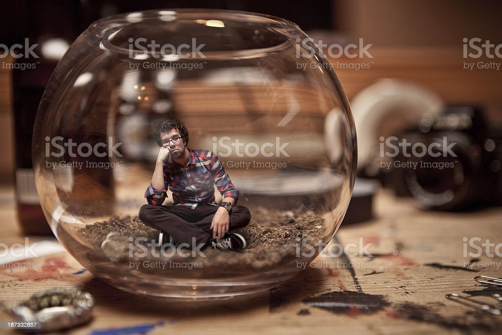 Unhappy Miniature man trapped inside a fishbowl. stock photo