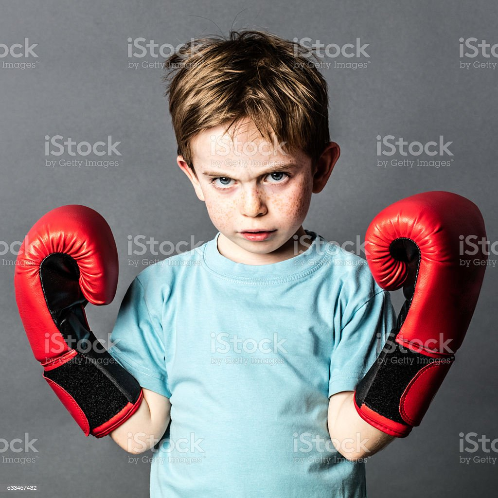 unhappy preschooler with red hair showing his boxing gloves stock photo