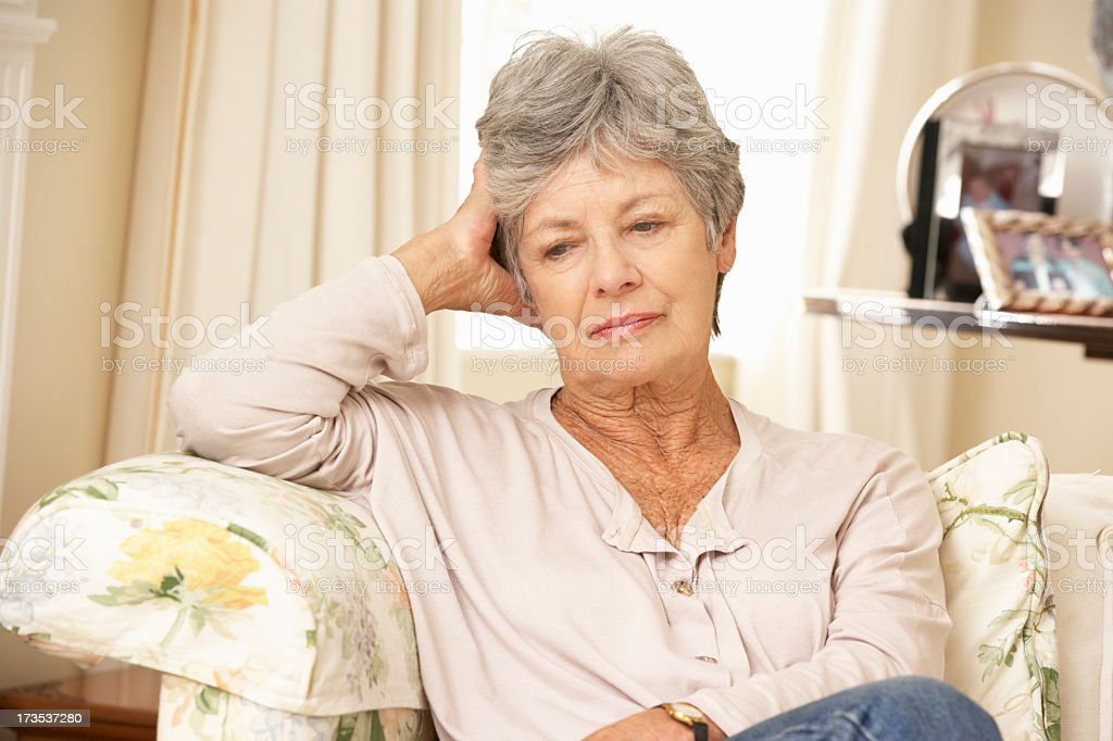 Unhappy Retired Senior Woman Sitting On Sofa At Home stock photo