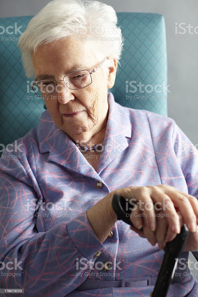 Unhappy Senior Woman Sitting In Chair Holding Walking Stick stock photo