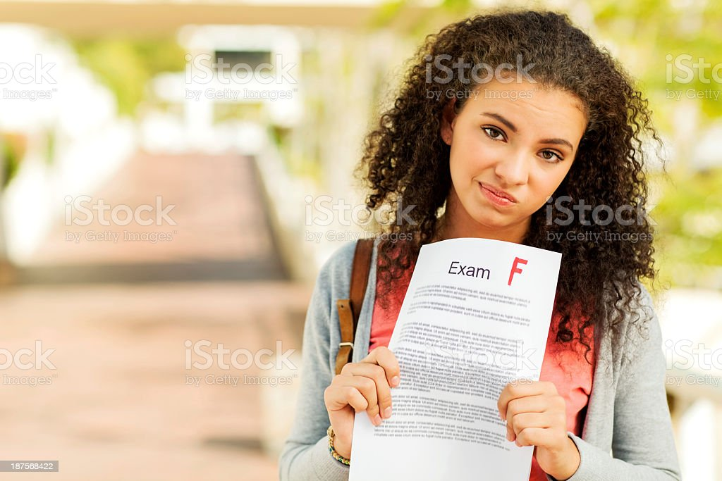 Unhappy Student Holding Exam Result With F Grade On Sidewalk stock photo