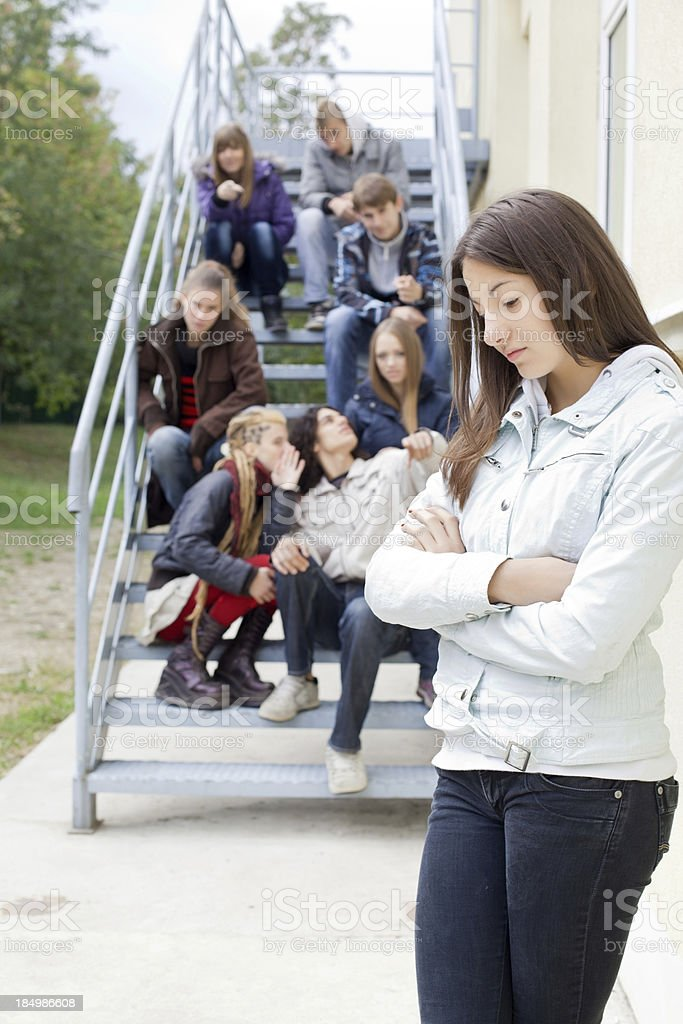 Unhappy teenage girl, her classmates gossiping on background. stock photo