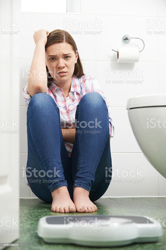 Unhappy Teenage Girl Looking At Bathroom Scales stock photo