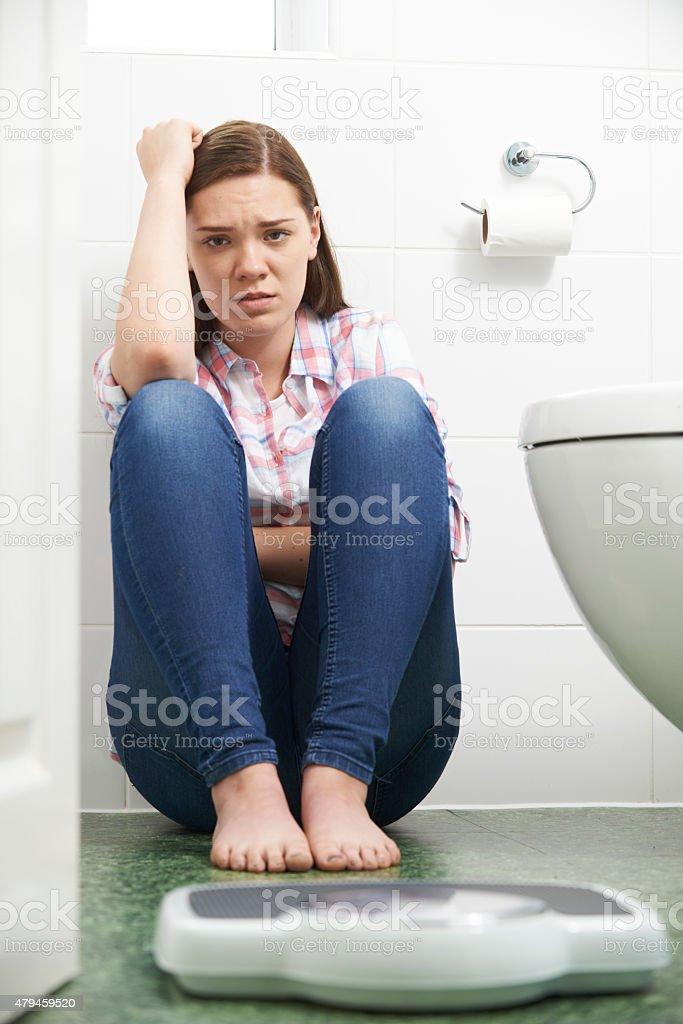 Unhappy Teenage Girl Looking At Bathroom Scales stock photo