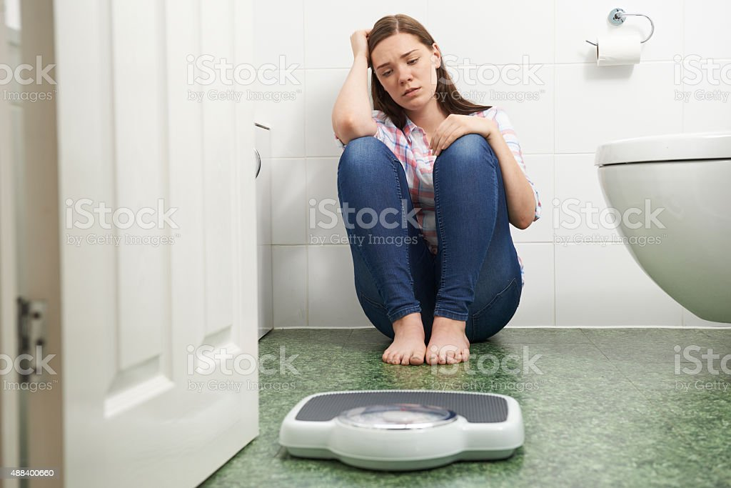 Unhappy Teenage Girl Sitting On Floor Looking At Bathroom Scales stock photo