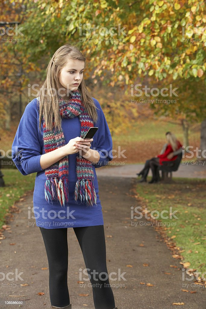 Unhappy Teenage Girl Standing In Autumn Park With Couple stock photo