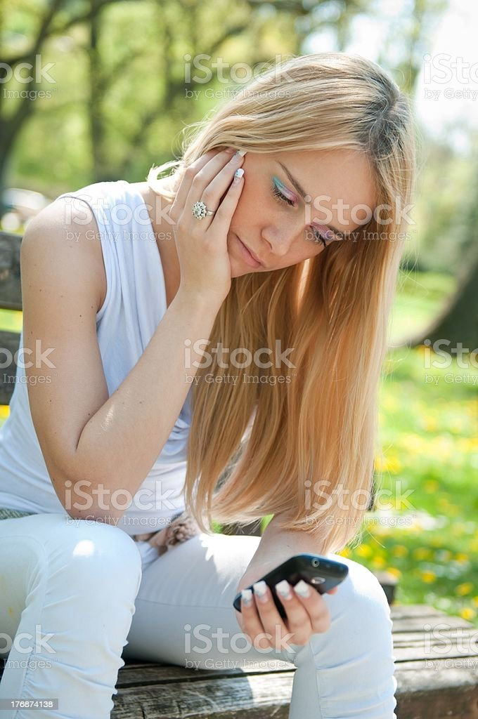 Unhappy teenager with mobile phone royalty-free stock photo